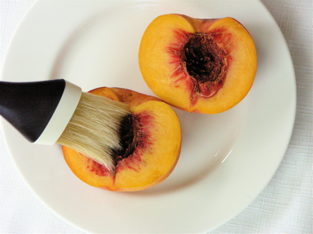Brush the peach halves with olive oil for grilling